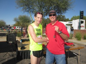 Double Down Race Directors presented Herndon Injury Lawyer Doug Landau with his medal after he completed the Runners Den 5km and 10km races in Phoenix, Arizona before the Association fort Justice CLE sessions resumed