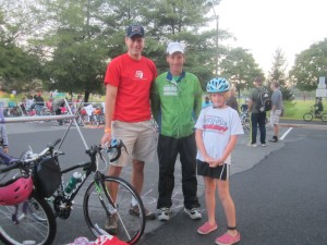 Volunteer, sponsor and sports safety advocate Doug Landau poses with a triathlete and parent who came from Richmond Virginia to participate in the Herndon Kids Triathlon