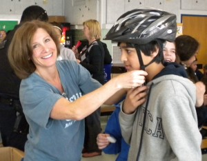 "Melissa Landau fitting a Herndon Elementary School student with a new bike helmet as part of the ABRAMS LANDAU ""putting lids on the kids"" head safety and brain injury prevention program"