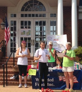 Herndon disability and injury lawyer Doug Landau collects his 2014 Fawn Lake Triathlon overall winner and Wounded Warrior medals after this Spotsylvania Virginia sprint race.