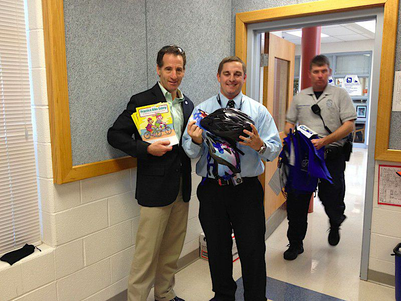 "Hutchison Elementary School's Assistant Principal Ross Baker and Herndon bike safety lawyer putting ""the lids on the kids"""