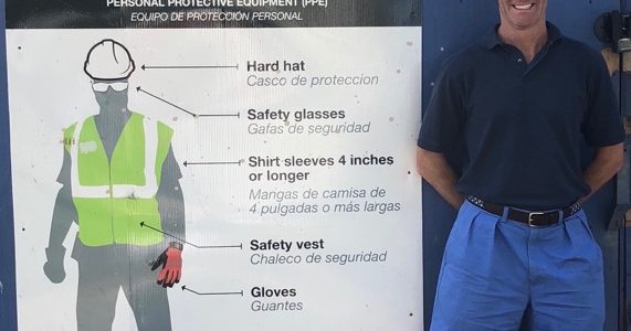 attorney doug landau next to a jobsite dress code sign