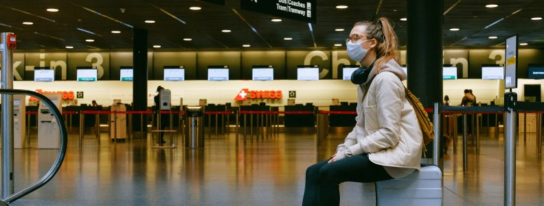 woman sitting on luggage at airport with mask