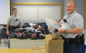 Herndon Bicycle Patrol Police Officers unpacking Bell Helmets to give to Hutchison Elementary School students as part of the bike safety program sponsored by the Herndon law firm ABRAMS LANDAU, the Virginia Trial Lawyers Foundation, and triathlon champion Henry Tragle