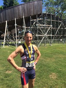 With the Quassey Amusement Park roller coaster behind him, Doug Landau shows his AG runners up medal at the USAT New England DUathlon Championships held in Middlebury, CT at the Pat Griskus races.