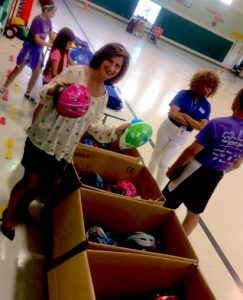 Melissa Landau giving out helmets at Guilford Elementary School May 31, 2017.