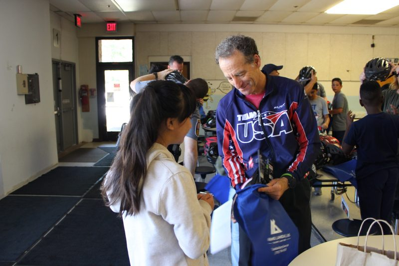 doug landau giving away bike helmet at clearview elementary school