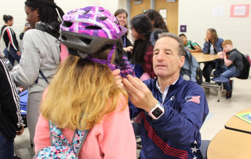 Doug Landau fitting helmet on student