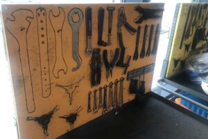 Tool wall showing variety of tools, with stenciled outlines indicating where each tool belongs
