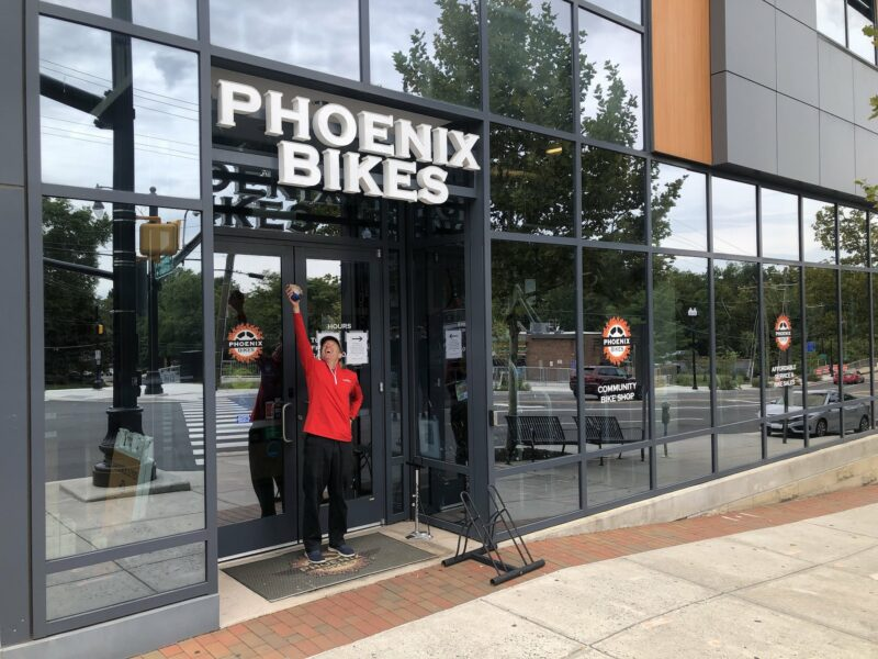 Mr. Landau posing in front of Phoenix Bikes shop. Image shows pretty all glass exterior of the business.