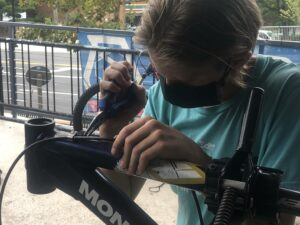 Aelin, young mechanic in Earn-a-Bike program for Phoenix Bikes, stripping bikes of parts