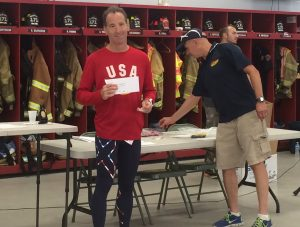 Even a small check helps. Here Social Security disability lawyer Doug Landau holds his medal & check from the Vincentown, New Jersey Triathlon