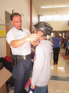 Police officers helped fit Herndon sixth graders with new bike helmets to help prevent brain injury