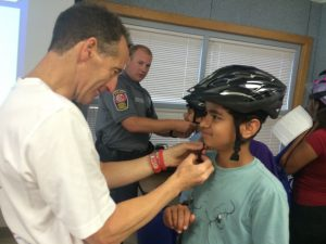 """It takes lots of """"hands on"""" helpers to properly fit each student with their FREE bicycle helmet at the ABRAMS LANDAU & Virginia Trial Foundation's brain injury prevention programs"""